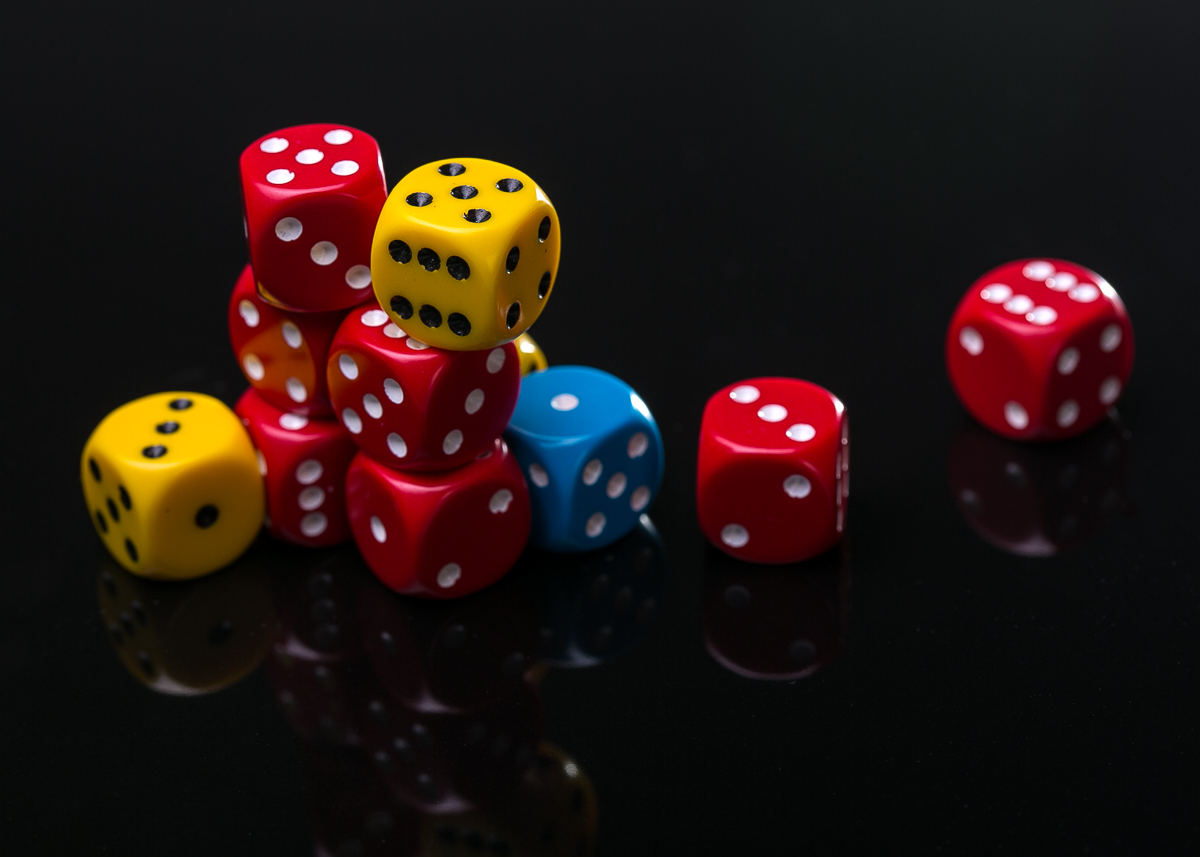 Coloured dice on shiny black surface