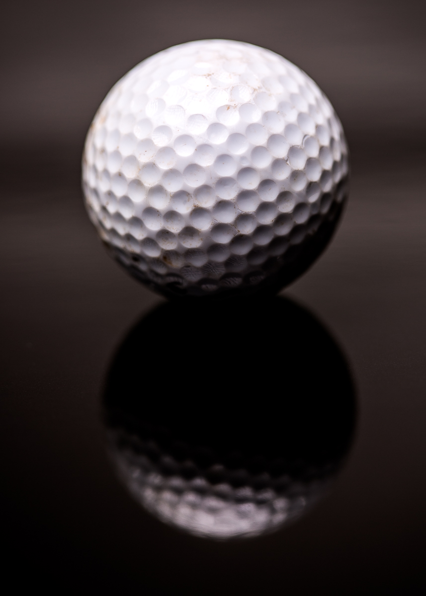 Close up of golf ball on shiny black surface